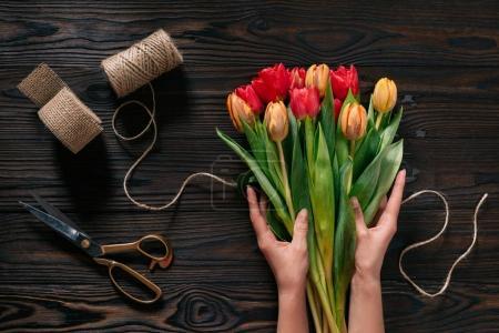 Foto de Vista parcial de manos femeninas, cuerda, tijeras y ramo de flores en la superficie de madera - Imagen libre de derechos