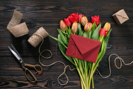 flat lay with bouquet of tulips, envelope and decoration supplies on wooden tabletop