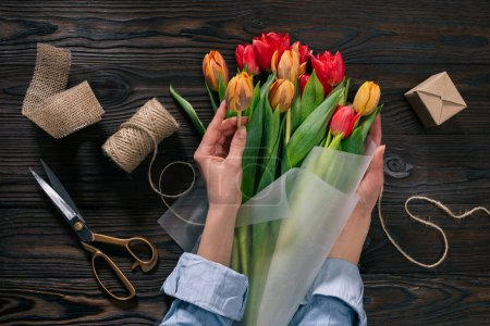partial view of woman wrapping bouquet of tulips into wrapping paper on wooden tabletop