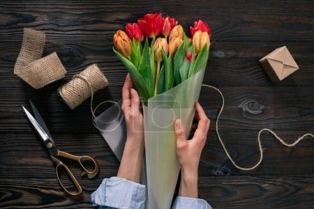 Photo for Partial view of woman wrapping bouquet of tulips into wrapping paper on wooden tabletop - Royalty Free Image