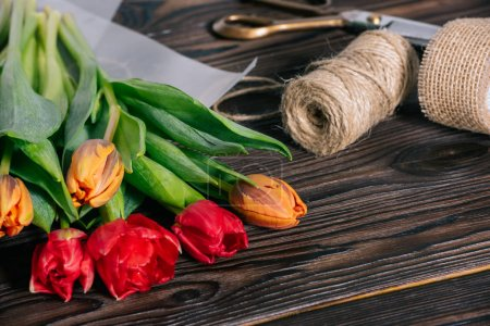 close up view of bouquet of tulips, ribbon, scissors and rope on wooden tabletop