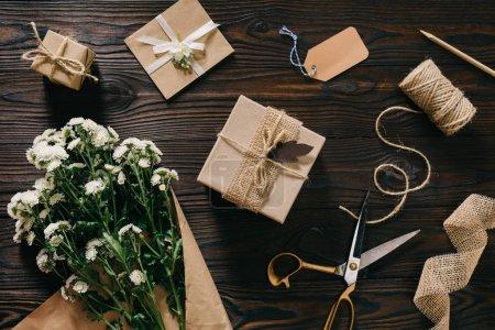 Photo pour Lay plat avec des cadeaux emballés, bouquet de fleurs, de corde et de ciseaux sur la surface en bois - image libre de droit