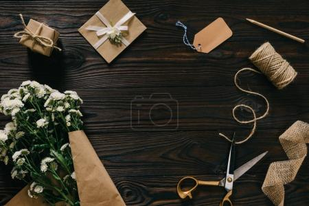 flat lay with wrapped present, bouquet of flowers, rope and scissors on wooden surface