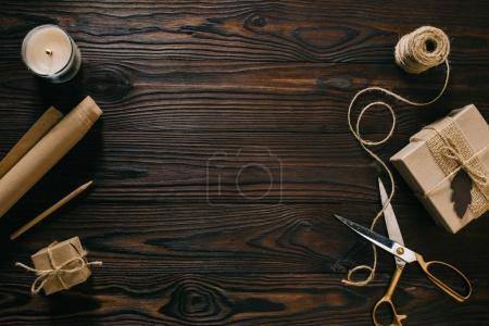 flat lay with wrapped presents, rope and scissors on wooden surface