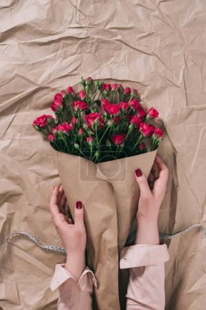 Teilansicht weiblicher Hände und Rosenstrauß in Bastelpapier