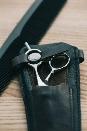 close up view of scissors and comb for hairstyling on wooden tabletop
