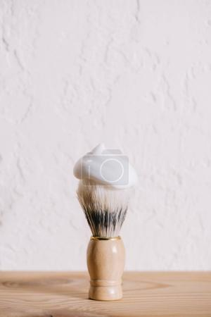 close up view of shaving brush with foam against white wall