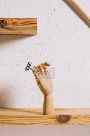 close up view of decorative wooden hand with blade on shelf