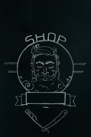 close up view of drawn emblem of bearded man on blackboard