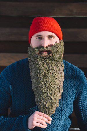 portrait of man with beard made of wood bark looking at camera outdoors