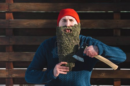 portrait of man with beard made of wood bark and axe in hand looking at camera outdoors