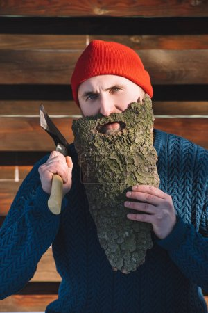 portrait of man with beard made of wood bark and axe in hand outdoors