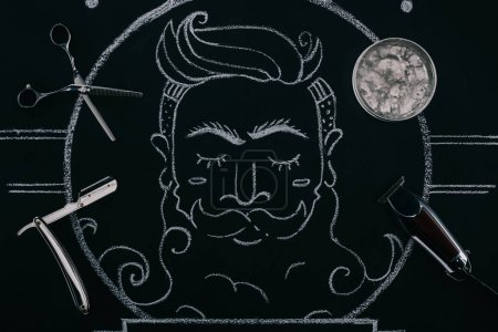 top view of arranged ice cubes in bowl, scissors, razor and drawn picture on blackboard