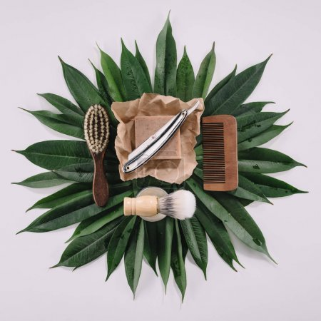 top view of arranged barber tools for shaving on green leaves isolated on grey