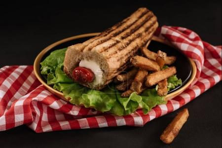 close-up shot of delicious french hot dog with fries on plate isolated on black