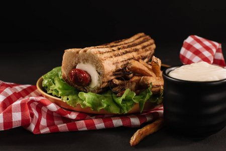 Photo for Still life with french hot dog with fries on plate isolated on black - Royalty Free Image