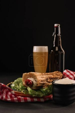 tasty french hot dog on plate with bottle and glass of beer isolated on black