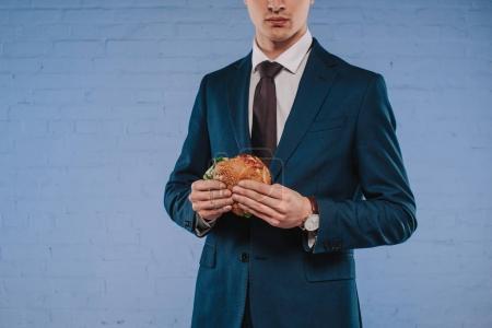 Photo pour Plan recadré de jeune homme d'affaires en costume tenant hamburger - image libre de droit