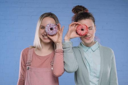 Photo for Smiling young women covering eyes with glazed doughnuts - Royalty Free Image