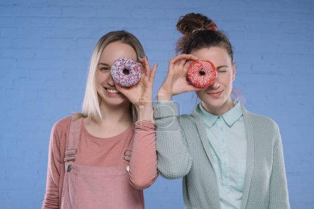 smiling young women covering eyes with glazed doughnuts