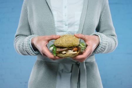 cropped shot of woman holding green vegan burger