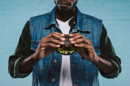 cropped shot of african american man holding tasty black burger