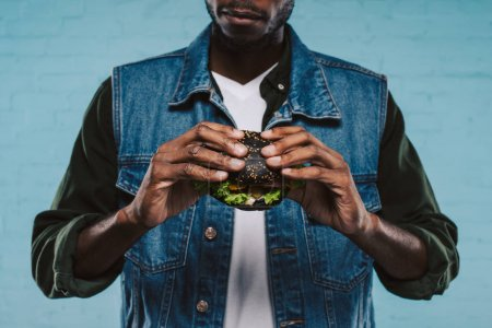 Photo for Cropped shot of african american man holding tasty black burger - Royalty Free Image