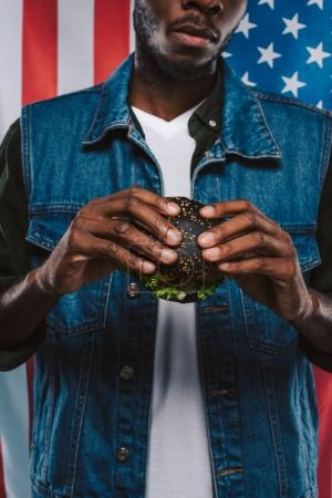cropped shot of african american man holding black burger against usa flag
