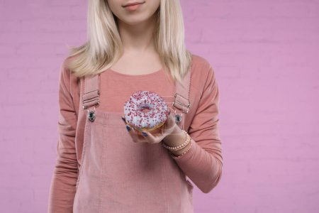 cropped shot of woman holding delicious glazed doughnut