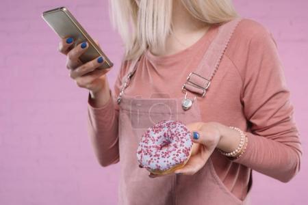 Photo pour Plan recadré de jeune femme avec beignet et smartphone - image libre de droit