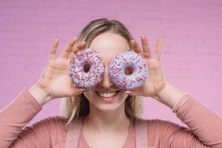 smiling young woman covering eyes with doughnuts in front of pink brick wall