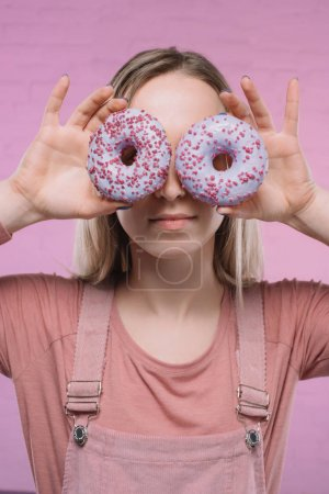 attractive young woman covering eyes with doughnuts