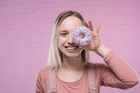 happy young woman covering one eye with glazed doughnut