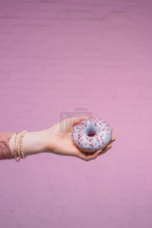 cropped shot of woman holding glazed doughnut in hand in front of pink brick wall