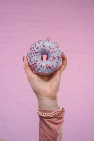cropped shot of woman holding tasty glazed doughnut in hand