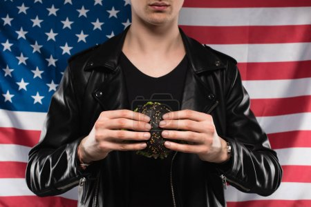 cropped shot of young man in leather jacket holding black burger against usa flag
