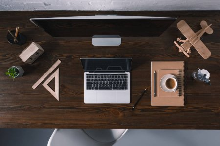 Photo for Top view of desktop computer, laptop and office supplies on wooden table - Royalty Free Image