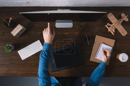 Photo for Cropped shot of person using desktop computer and taking notes at workplace - Royalty Free Image