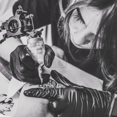 Black and white photo of woman tattoo during tattooing process