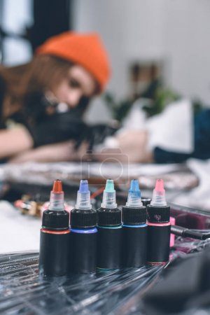 Photo for Bottles of ink in front of working tattoo master - Royalty Free Image