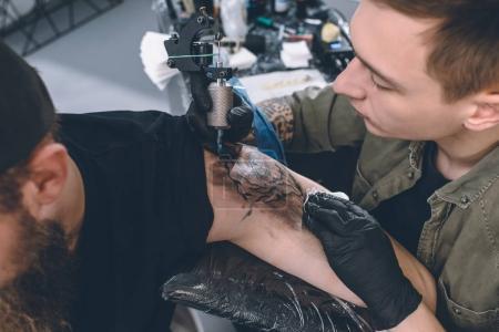 Photo pour Homme barbu et tatouage master au cours de processus dans le studio de tatouage - image libre de droit