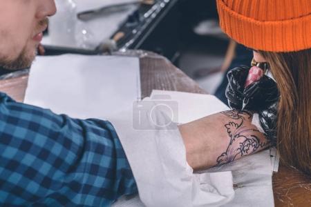 Tattoo artist in gloves working on arm piece in studio