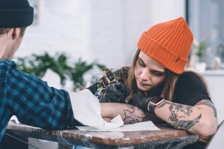 Young man and female tattoo master during tattooing process in studio