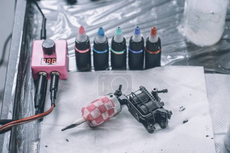 Tattoo artist workplace with machine and bottles with colorful tattoo ink