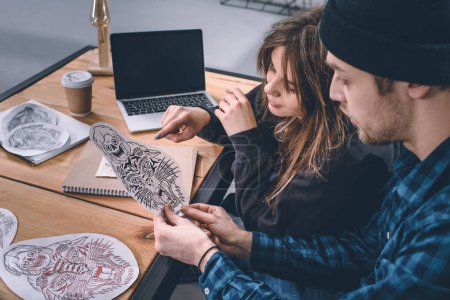 Photo for Young couple choosing tattoo design in studio - Royalty Free Image