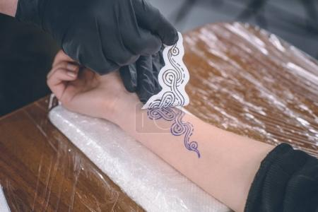 Cropped view of male tattoo artist working with sketch for arm