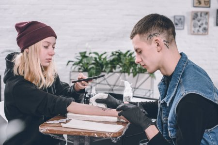 Young woman taking photo of tattooing process in studio