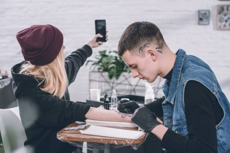Girl taking selfie of tattooing process in studio