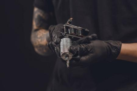 Photo for Male hands in gloves holding tattoo machine isolated on black - Royalty Free Image
