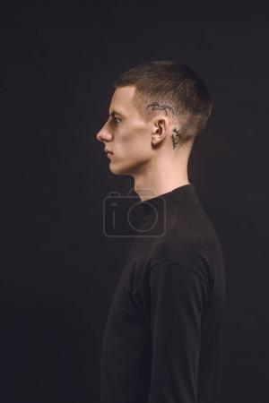 Side view of man with tattoo on temple isolated on black